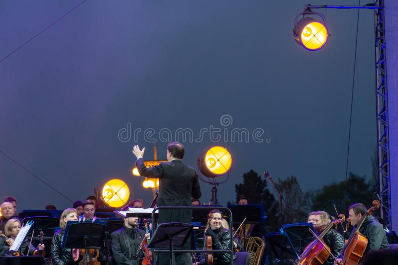 Conductor directing symphony orchestra with performers on background. Russia, Moscow, April 30, 2019: Conductor directing symphony orchestra with performers on royalty free stock photos