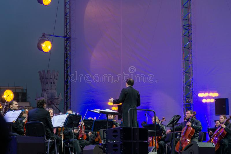 Conductor directing symphony orchestra with performers on background. Russia, Moscow, April 30, 2019: Conductor directing symphony orchestra with performers on stock images