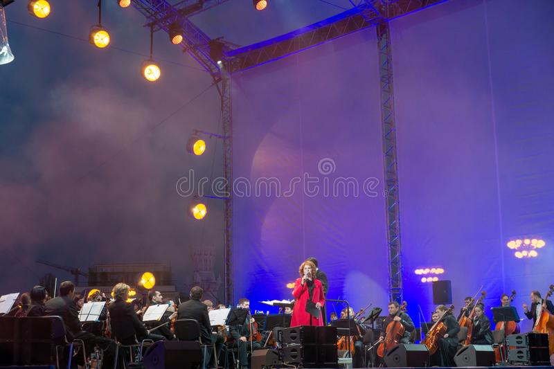 Conductor directing symphony orchestra with performers on background. Russia, Moscow, April 30, 2019: Conductor directing symphony orchestra with performers on stock image