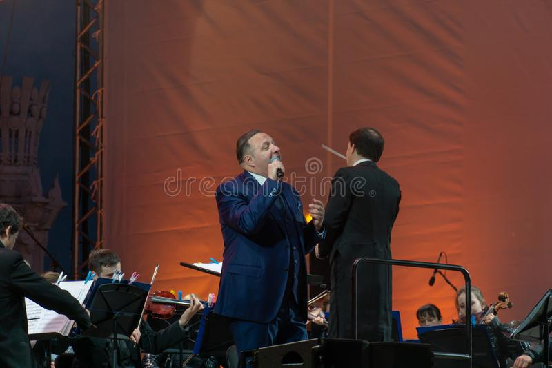 Conductor directing symphony orchestra with performers on background. Russia, Moscow, April 30, 2019: Conductor directing symphony orchestra with performers on royalty free stock images