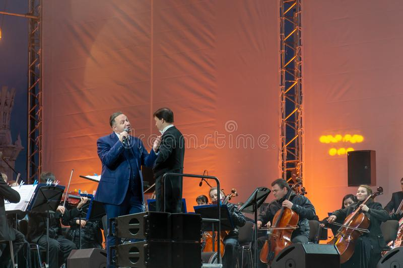 Conductor directing symphony orchestra with performers on background. Russia, Moscow, April 30, 2019: Conductor directing symphony orchestra with performers on stock photography