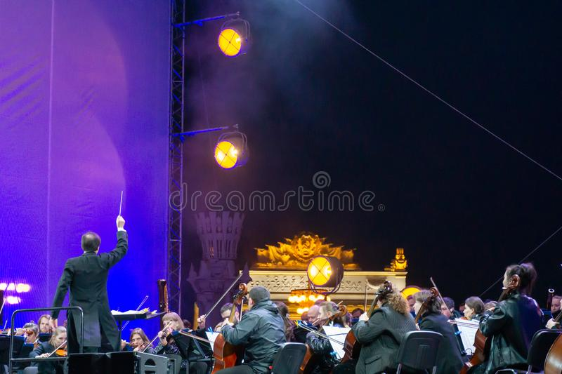 Conductor directing symphony orchestra with performers on background. Russia, Moscow, April 30, 2019: Conductor directing symphony orchestra with performers on royalty free stock photography