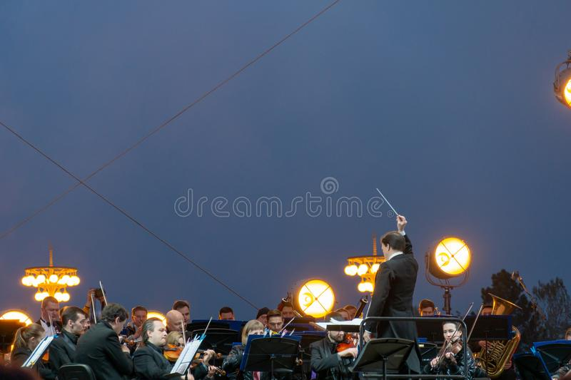 Conductor directing symphony orchestra with performers on background. Russia, Moscow - April 2019: Conductor directing symphony orchestra with performers on stock photos