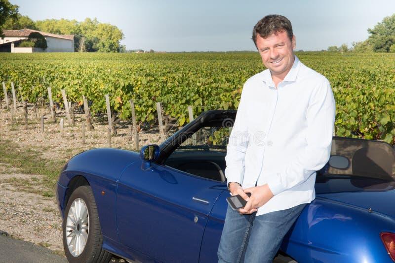 Conductor feliz del hombre que conduce el coche adulto masculino joven del lujo del nuevo propietario del coche convertible azul imagen de archivo libre de regalías