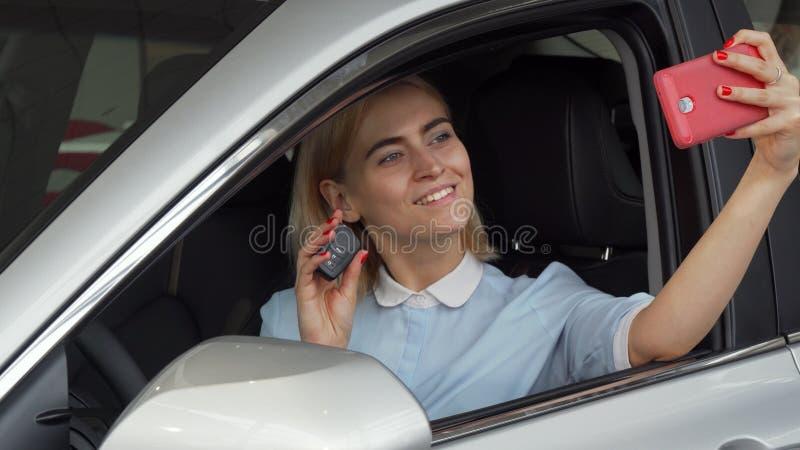 Conductor femenino hermoso que toma selfies con sus llaves del coche imagen de archivo