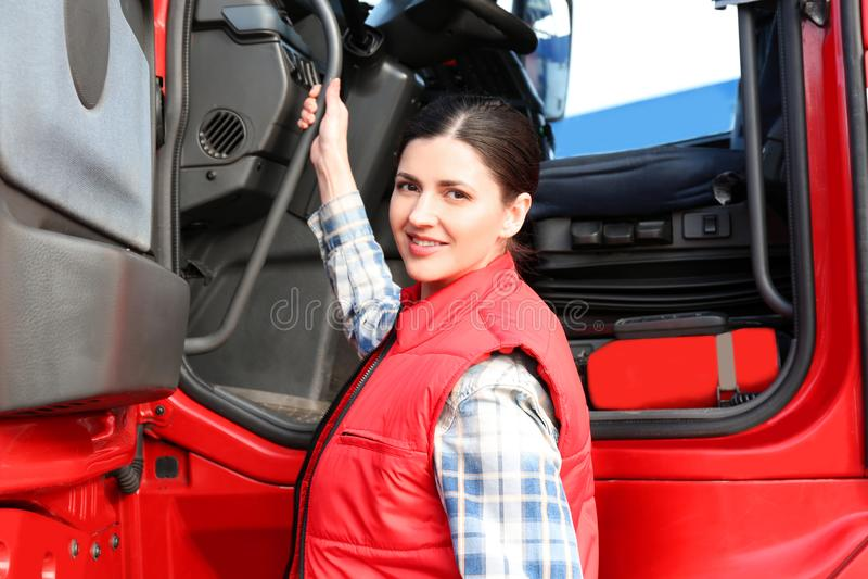 Conductor femenino joven cerca del camión moderno grande imagen de archivo