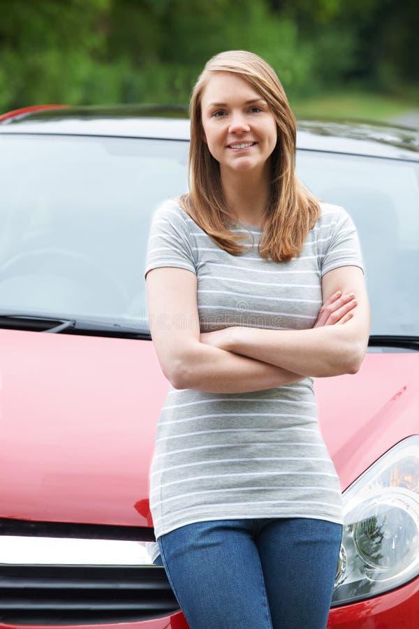 Conductor femenino joven orgulloso Standing In Front Of Car imagenes de archivo