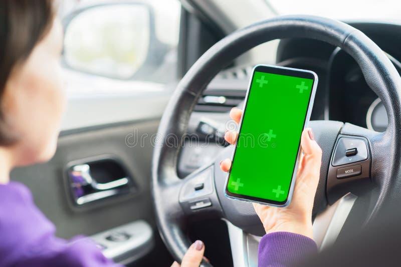 Conductor femenino joven que usa smartphone de la pantalla t?ctil en un coche llave verde de la croma en la exhibición del teléfo foto de archivo