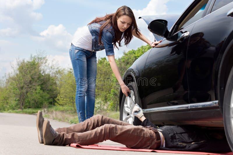 Conductor femenino que ayuda a un mecánico en su coche fotos de archivo