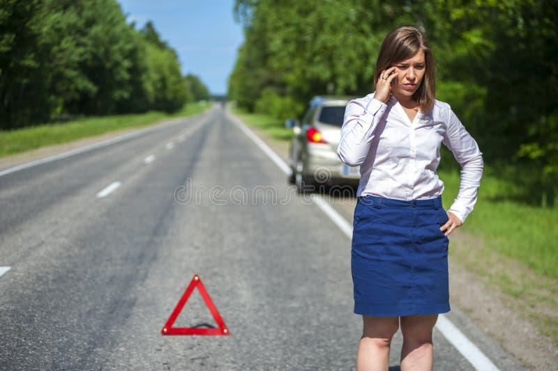 Conductor femenino que llama a una ayuda del coche después de avería foto de archivo