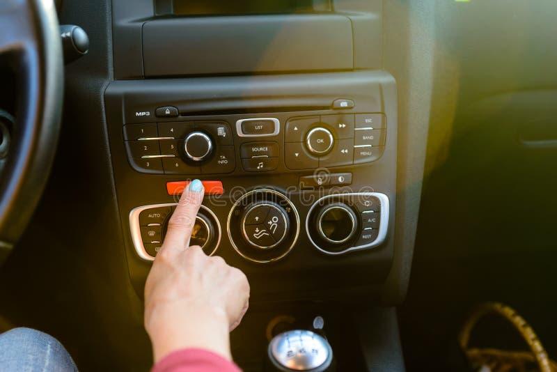 Conductor femenino que presiona un botón rojo del peligro imagen de archivo libre de regalías