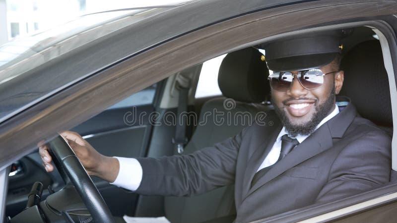 Conductor masculino negro que se sienta en coche y que sonríe en la cámara, servicio del transporte foto de archivo