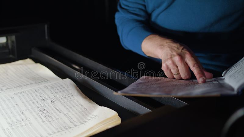 Conductor in an Orchestra Pit Studies Sheet Music. Lviv, Ukraine - June, 2017: Close up hands of mid aged conductor alone in dark orchestra pit studies sheet stock photos