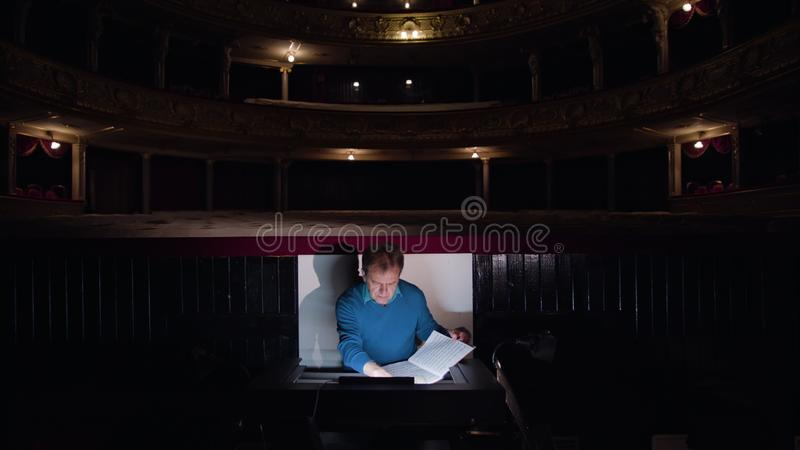 Conductor in an Orchestra Pit Studies Sheet Music. Lviv, Ukraine - June, 2017: Mid aged conductor alone in dark orchestra pit studies sheet music and tweets the stock images