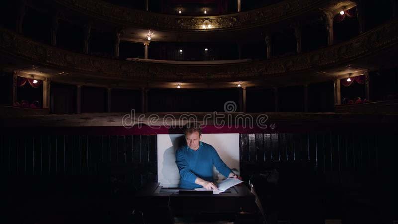 Conductor in an Orchestra Pit Studies Sheet Music. Mid aged conductor alone in dark orchestra pit studies sheet music and tweets the tune. Indoor. Medium royalty free stock photo