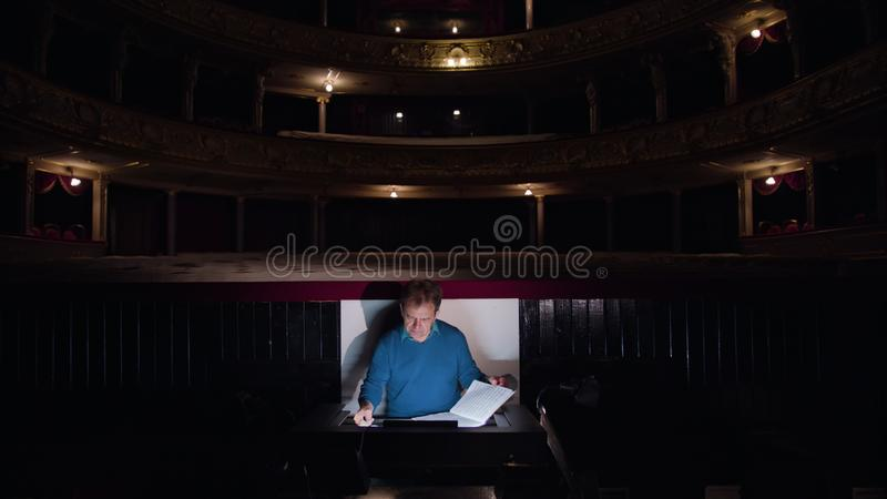 Conductor in an Orchestra Pit Studies Sheet Music. Mid aged conductor alone in dark orchestra pit studies sheet music and tweets the tune. Camera moves towards royalty free stock photo