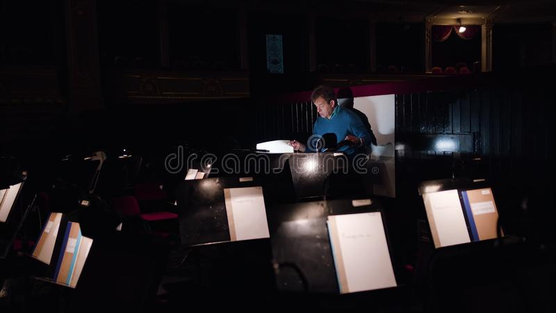 Conductor in an Orchestra Pit Studies Sheet Music. Mid aged conductor alone in dark orchestra pit studies sheet music and tweets the tune. Indoor. Wide angle stock images