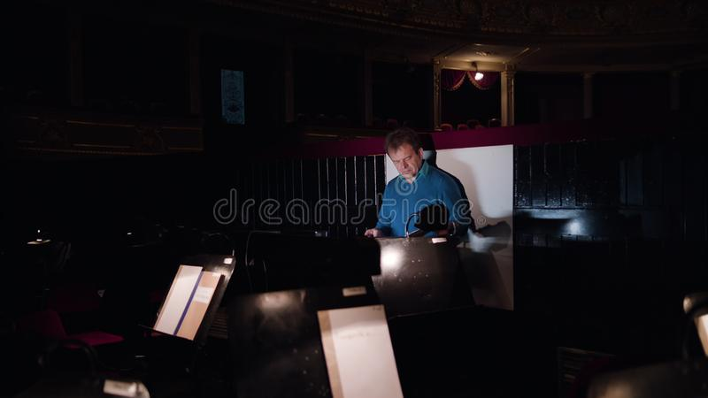 Conductor in an Orchestra Pit Studies Sheet Music. Mid aged conductor alone in dark orchestra pit studies sheet music and tweets the tune. Camera goes forward royalty free stock images