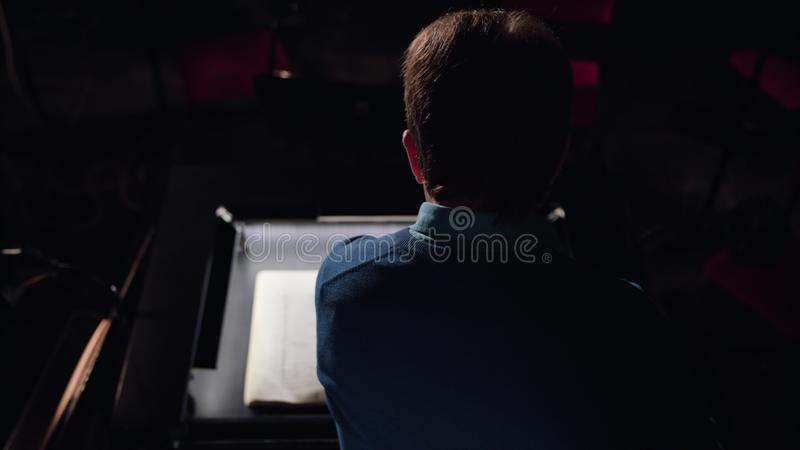 Conductor in an Orchestra Pit Studies Sheet Music. Mid aged conductor alone in dark orchestra pit studies sheet music and tweets the tune. Indoor. Medium. Camera royalty free stock photography