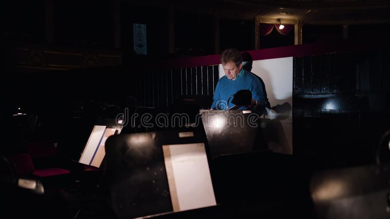 Conductor in an Orchestra Pit Studies Sheet Music. Mid aged conductor alone in dark orchestra pit studies sheet music and tweets the tune. Camera goes away stock images