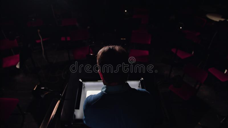 Conductor in an Orchestra Pit Studies Sheet Music. Mid aged conductor alone in dark orchestra pit studies sheet music and tweets the tune. Indoor. Medium. Camera stock photos
