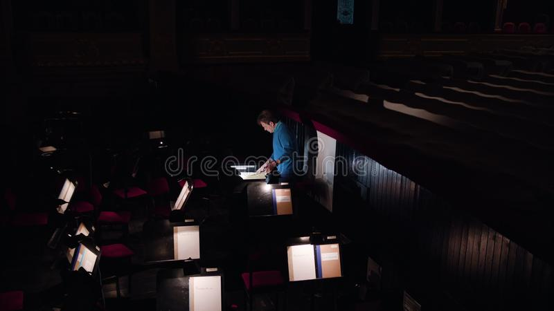 Conductor in an Orchestra Pit Studies Sheet Music. Mid aged conductor alone in dark orchestra pit studies sheet music and tweets the tune. Camera moves from royalty free stock photography