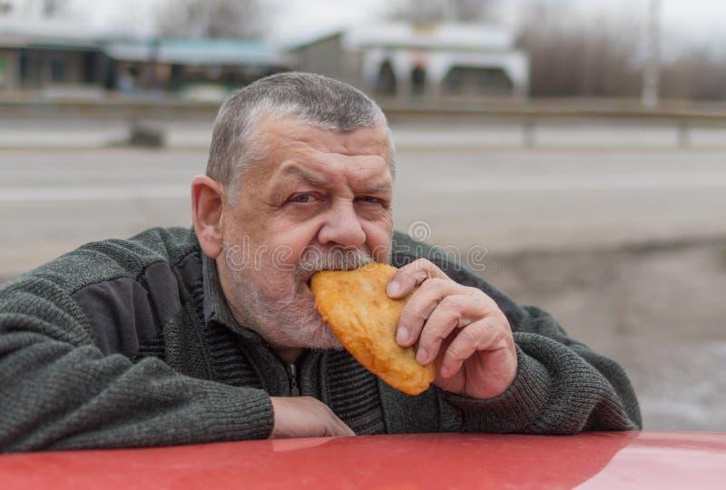 Conductor que come la empanada que inclina sus codos en el tejado del coche fotografía de archivo libre de regalías