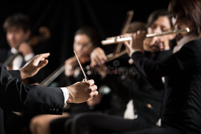 Conductor que dirige a la orquesta sinfónica fotos de archivo