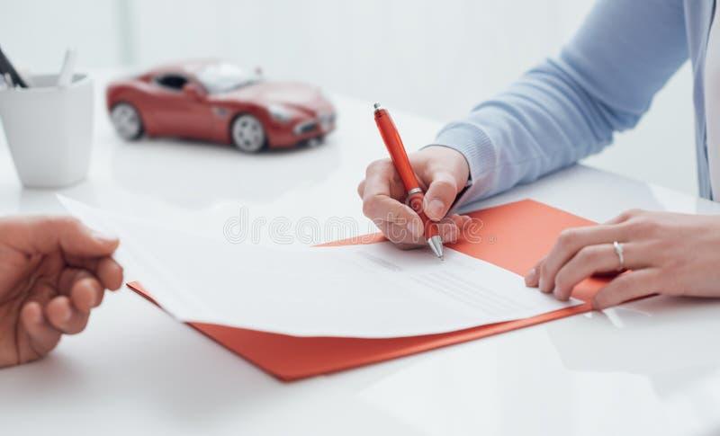 Conductor que firma un seguro de coche imágenes de archivo libres de regalías