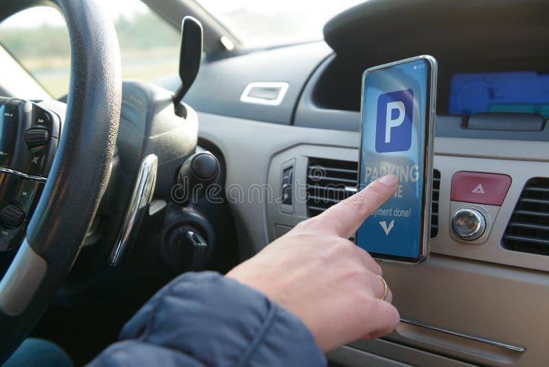 Conductor que usa el app del smartphone para pagar parquear foto de archivo libre de regalías