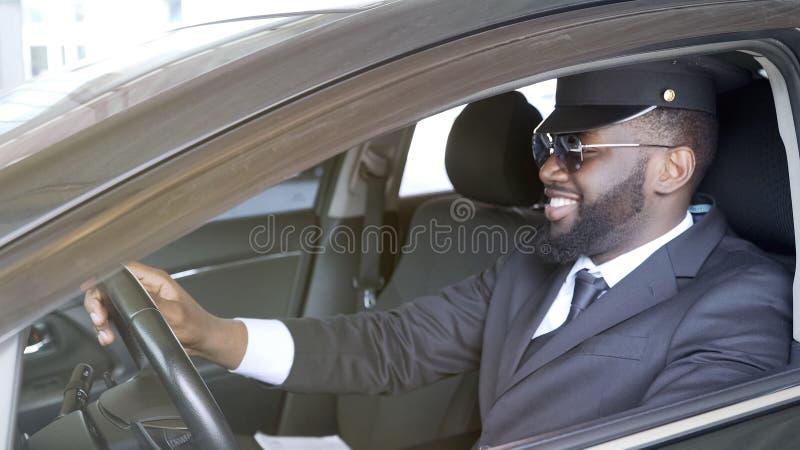 Conductor sonriente del negocio que se sienta en el automóvil de lujo, servicio del transporte foto de archivo libre de regalías