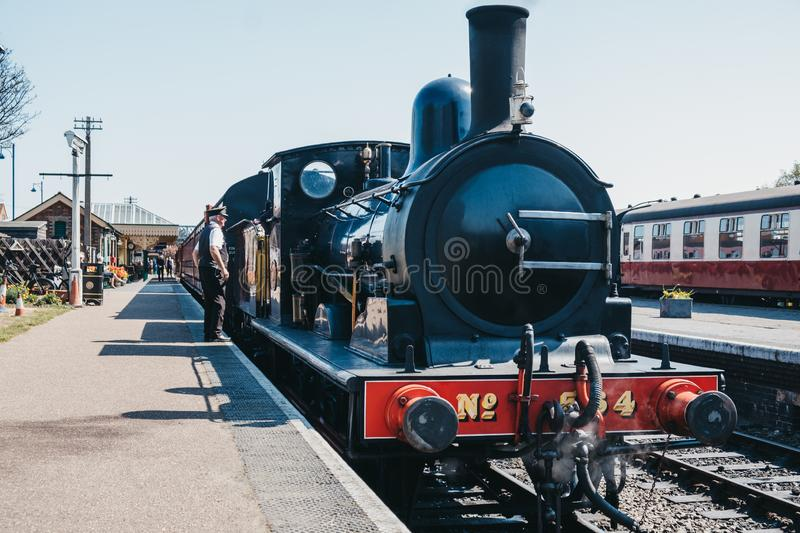 Conductor standing by the cab of The Poppy Line train, Sheringham, Nortfolk, UK stock photos