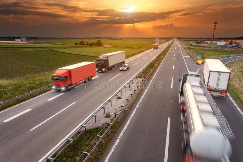 Conduire des camions dans la tache floue de mouvement sur la route au coucher du soleil image stock