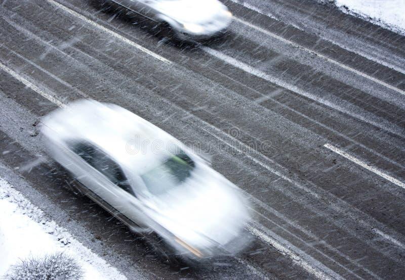 Conduire des voitures sur la rue neigeuse de ville dans la tache floue de mouvement photographie stock