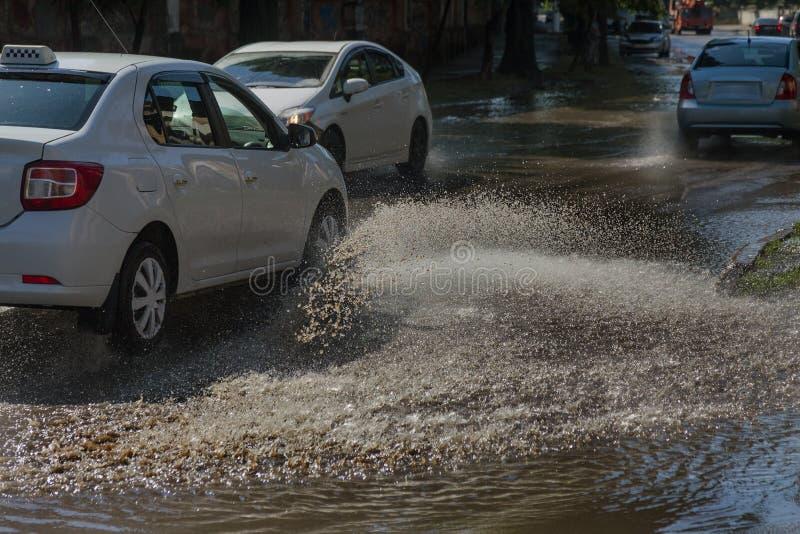 Conduire des voitures sur une route inondée pendant les inondations provoquées par la pluie fulmine Flotteur de voitures sur l'ea images libres de droits