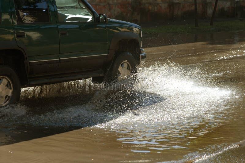 Conduire des voitures sur une route inondée pendant les inondations provoquées par la pluie fulmine Flotteur de voitures sur l'ea image stock