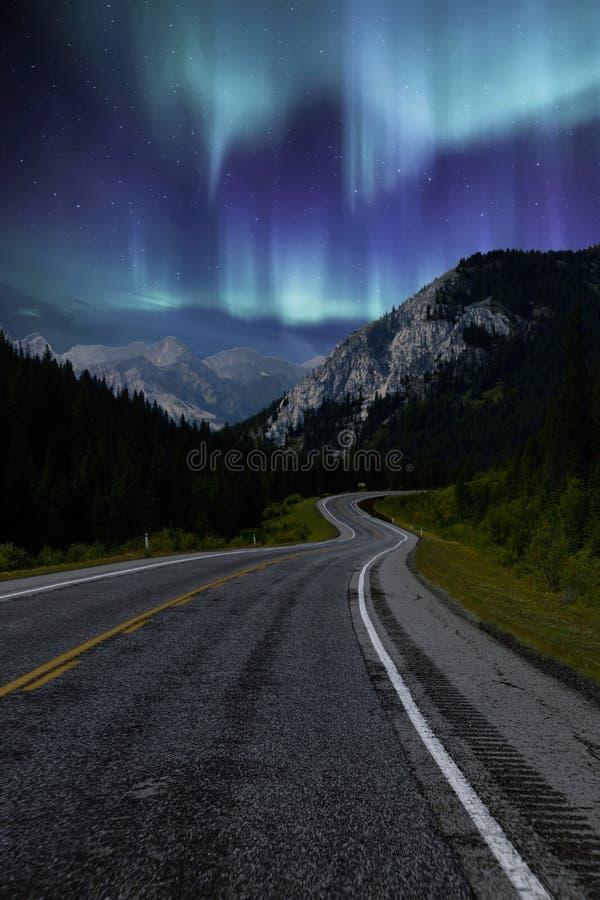 Conduire le long de la route la nuit avec Northern Lights dans le ciel photo libre de droits