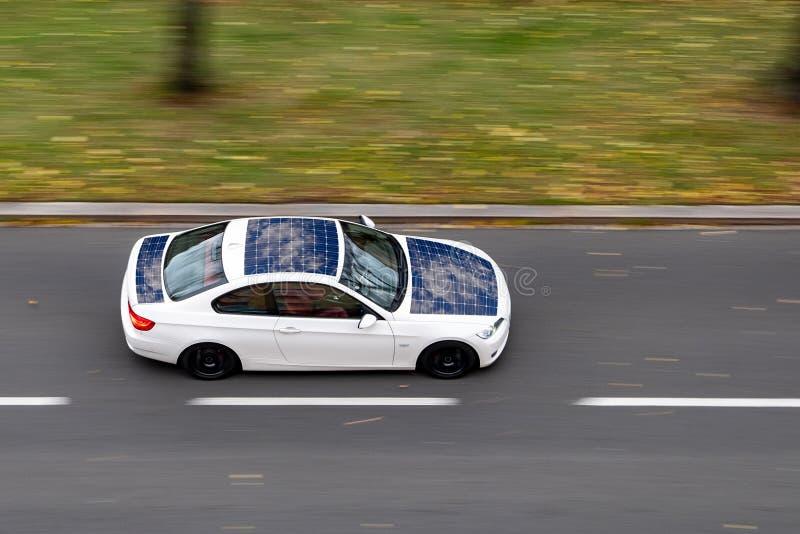 Conduire très rapidement la voiture solaire électrique écologique blanche sur une rue de ville L'image est prise avec un effet fo images stock