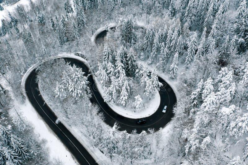 Conduisant sur la cuvette de routes d'hiver une route d'enroulement de forêt dans les montagnes photo stock
