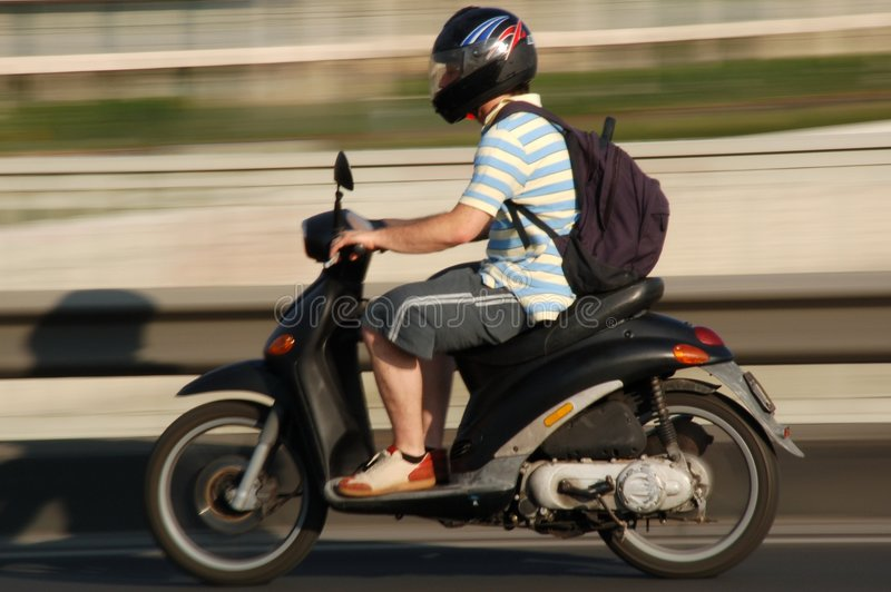 Conduite de garçon un scooter photo libre de droits