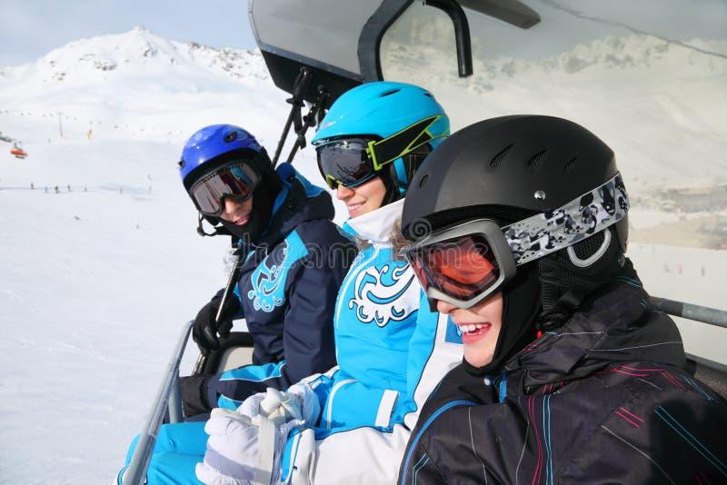 Conduite de sourire de trois skieurs sur funiculaire photographie stock libre de droits