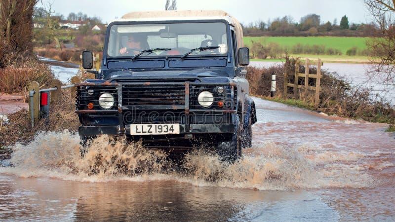 Conduite de véhicule par des eaux d'inondation sur la route photographie stock