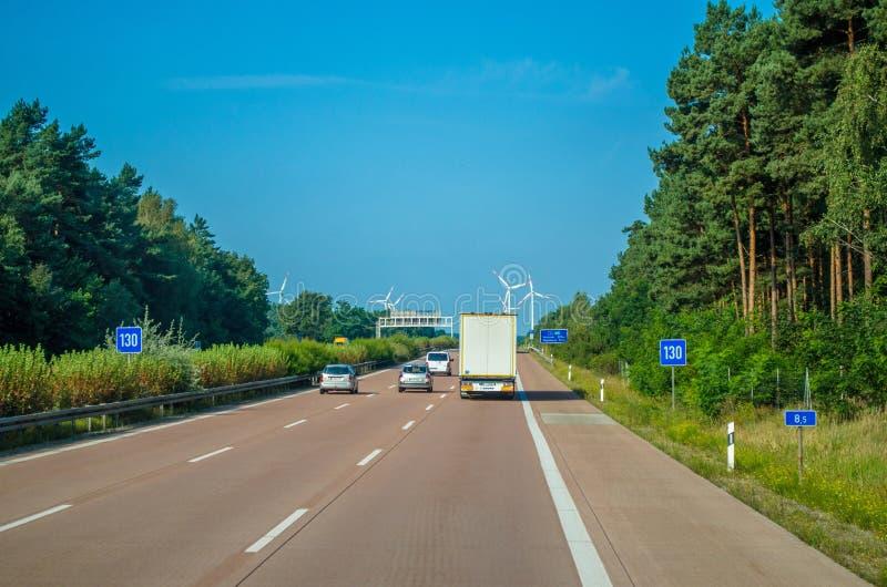 Conduite de véhicule sur l'autoroute vers des turbines de vent photo stock
