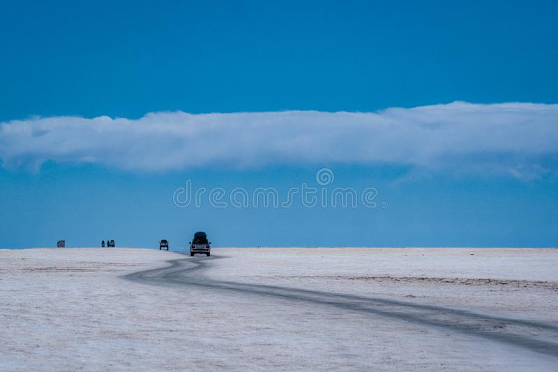 Conduite de véhicules par des appartements de sel de Salar de Uyuni images stock