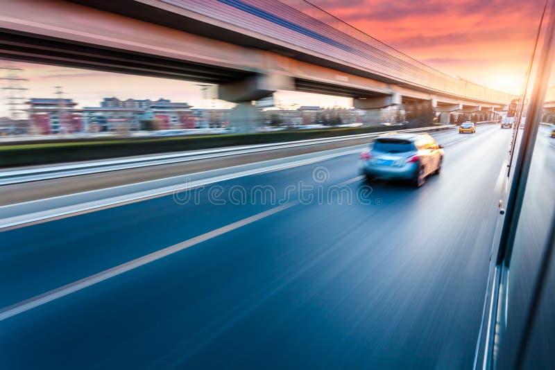 Conduite sur l'autoroute au coucher du soleil, tache floue de mouvement photo libre de droits