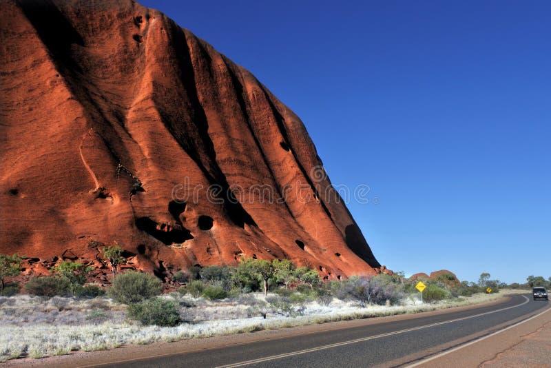 Conduite sur une route le long de roche d'Uluru Ayers dans le territoire national Australie d'Uluru-Kata Tjuta ParkNorthern photographie stock libre de droits