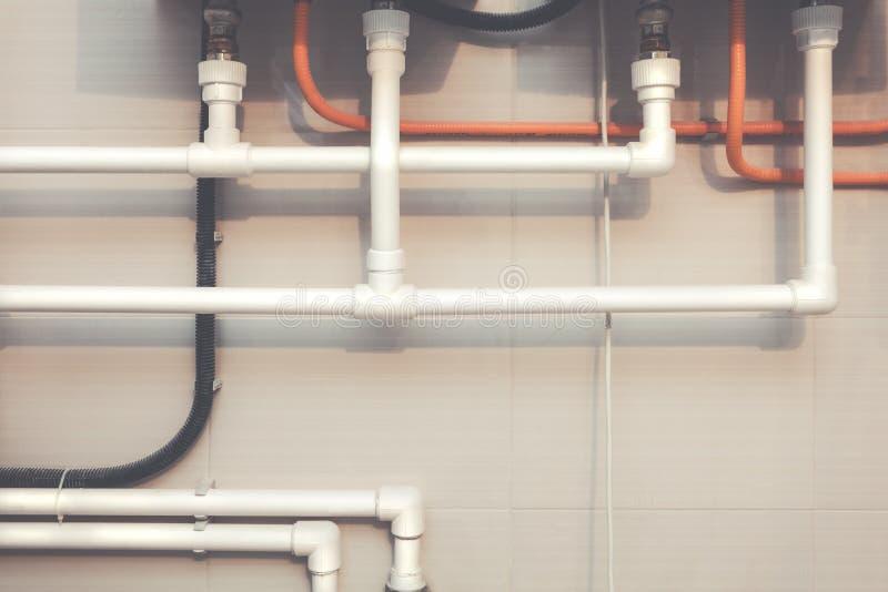 Conduites d'eau en plastique blanches de système de tuyauterie avec le montage de Y-branche, le tube ondulé noir et le mur avec l photographie stock libre de droits
