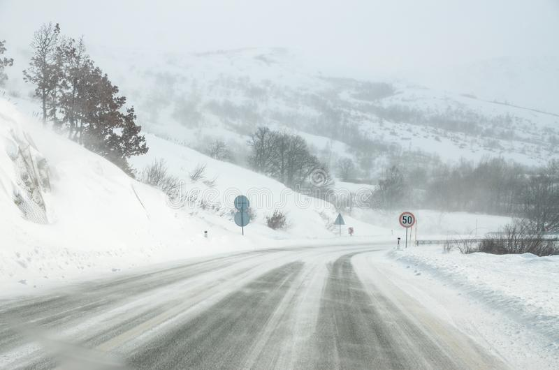 Condurre un'automobile sulla strada bianca e nevosa con un forte vento Scena e bufera di neve del tempo di inverno Tempesta di in immagini stock