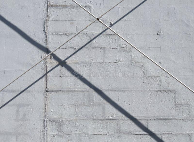 Conduttura del metallo accanto ad un vecchio muro di cemento dipinto immagini stock libere da diritti