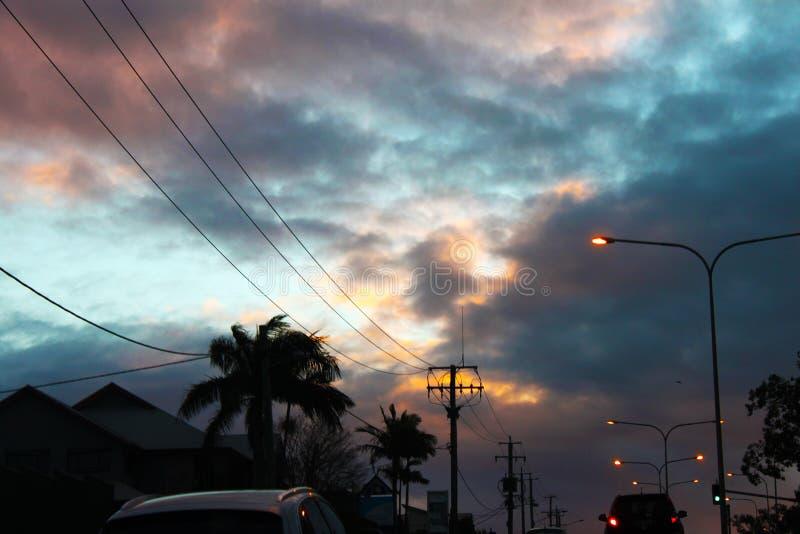 Conduza em casa no por do sol com o céu nebuloso tormentoso e as árvores tropicais que dirigem fora de Brisbane Austrália foto de stock royalty free
